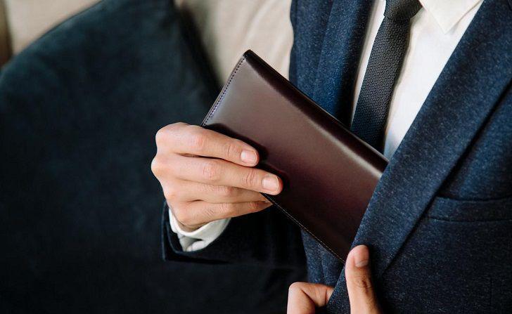スーツの内ポケットに財布を入れる男性